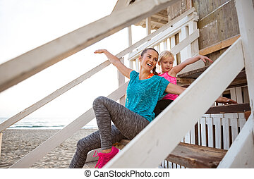 Mother and daughter sitting together at beach pretending to fly