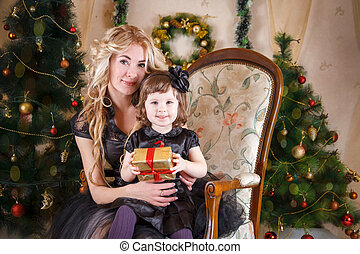 Mother and daughter sitting under Christmas tree