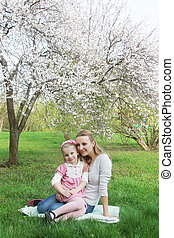 Mother and daughter sitting under spring tree