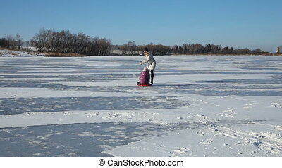 Mother and daughter sledding on frozen lake