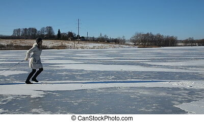 Mother and daughter sledding on frozen lake - Mother with...