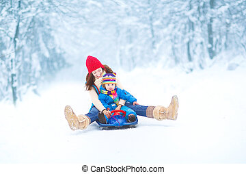 Mother and daughter sledging ride - Young happy mother and ...