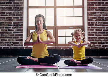 Mother and daughter smiling while doing yoga exercises...