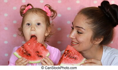 Mother and daughter smilling and eat watermelon, of playing...