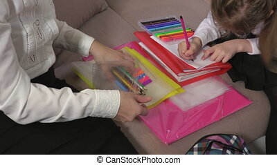 Mother and daughter sorting pencils and notebooks for School