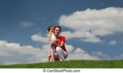 Mother and daughter squat on meadow embracing
