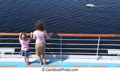 Mother and daughter stand on deck of ship looking at boat