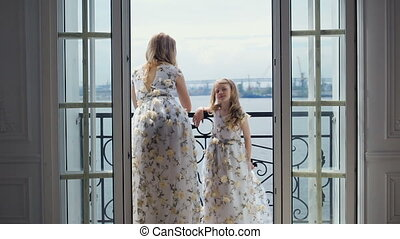 mother and daughter stand one against the other in front of a big open window