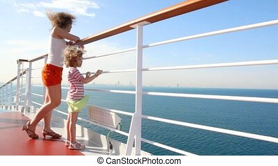 mother and daughter stands on deck of cruise ship