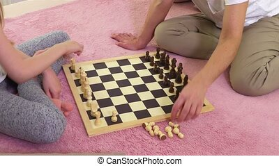 Mother and daughter start to play chess