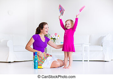 Mother and daughter sweeping the floor - Young happy mother...