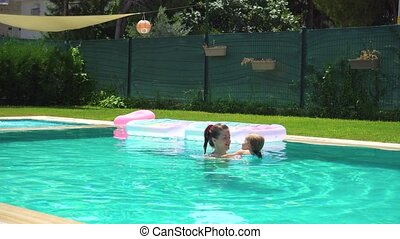 Mother and daughter swimming in pool at backyard - Woman and...