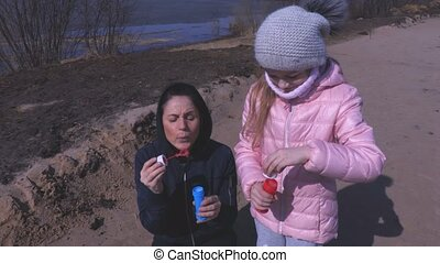Mother and daughter take fun with soap bubbles