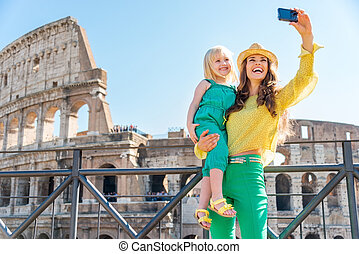 Mother and daughter taking a selfie at the Colosseum in Rome...