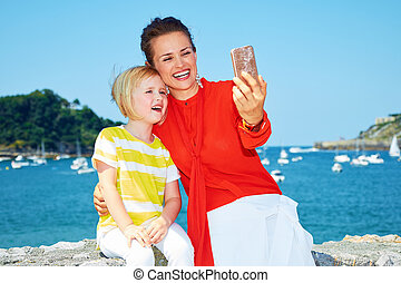 Mother and daughter taking selfie in front of lagoon