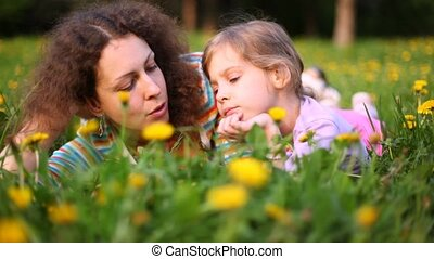 Mother and daughter talk lying on lawn in sunny weather
