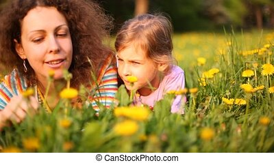 Mother and daughter talk lying on lawn with dandelions