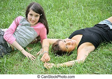 mother and daughter-teenager lie on the grass 2
