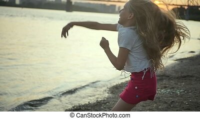 Mother and daughter throw stones into the river. Happy moments of motherhood. Young mother and daughter on the city promenade during sunset. A cheerful girl jumps fervently with happiness. Slow motion.
