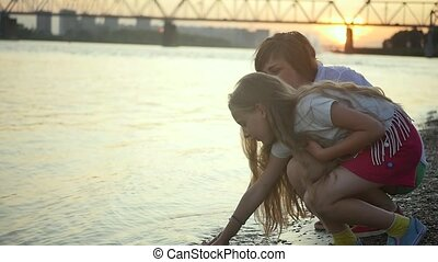 Mother and daughter throw stones into the river. Happy moments of motherhood. Young mother and daughter on the city promenade during sunset. Slow motion.