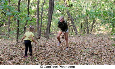 Mother and daughter throwing leaves