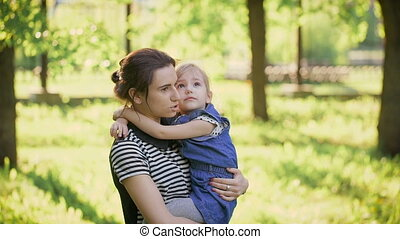 Mother and daughter together in the park. Beautiful slim girl holding a little girl in her arms.