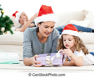 Mother and daughter unwrapping a present lying on the floor