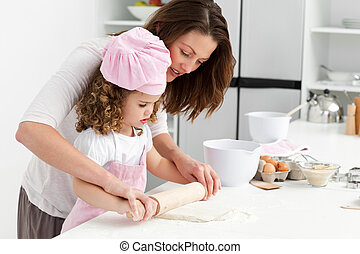 Mother and daughter using a rolling pin together in the...