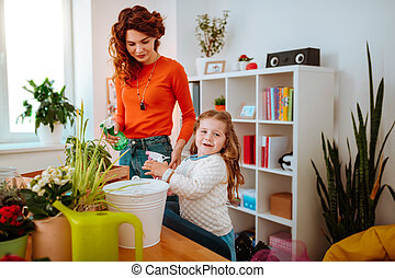 Using water diffusers. Mother and daughter using water diffusers while watering home plants together