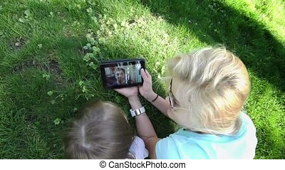 Mother and daughter using digital tablet to communicate with his father