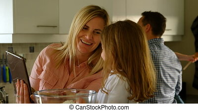 Mother and daughter using digital tablet while preparing food 4k