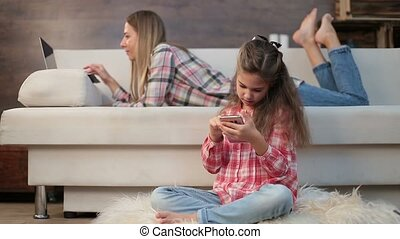 Mother and daughter using laptop and phone at home -...