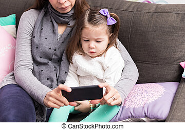 Mother And Daughter Using Mobile Phone On Sofa