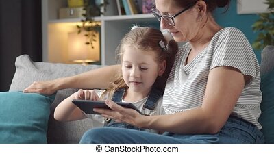 Mother and daughter using tablet while sitting on sofa