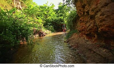 Mother and Daughter Walk along Stream in Rocks Shade