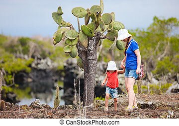 Mother and daughter walking at scenic terrain