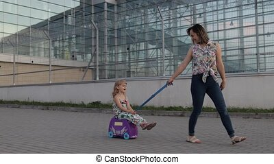 Caucasian mother and daughter walking outdoors from international airport terminal. Woman rides baby child on suitcase luggage on wheels. Girl and mom after departure from vacation, trip, holidays