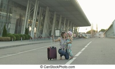 Caucasian mother and little daughter walking outdoors from international airport terminal. Woman carrying suitcase luggage on wheels. Child girl and mom after departure from vacation, trip, holidays