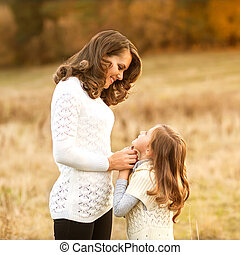 mother and daughter walking in autumn in a field