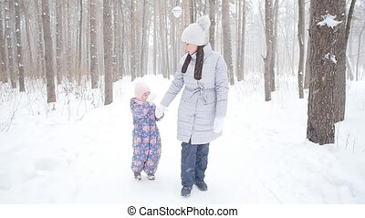 Mother and Daughter Walking in Snowy Forest or Park - Mother...