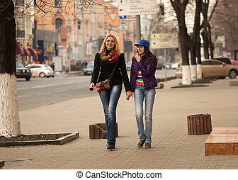 Mother and daughter walking in the city