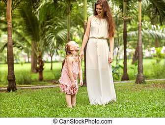 mother and daughter walking in the park, happy at sunset in Bang