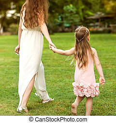 mother and daughter walking in the park holding hands in love