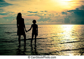mother and daughter walking on the beach at the dawn time