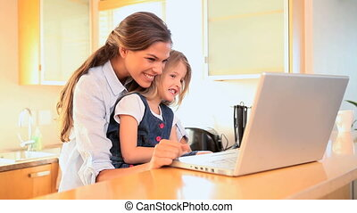 Mother and daughter watching a video on a laptop