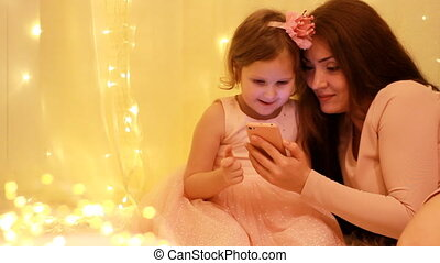 Mother and daughter watching video on smartphone on the...
