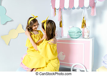 Mother and daughter wearing the same yellow dress.
