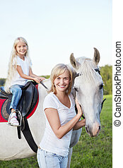 Mother and daughter with a horse