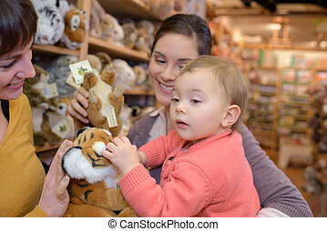 mother and daughter with attractive vendor in toy store