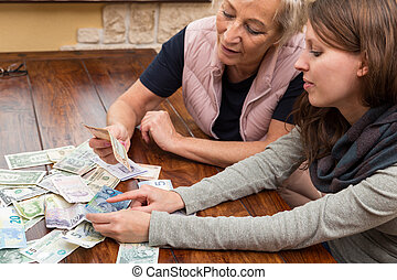 mother and daughter with bank notes